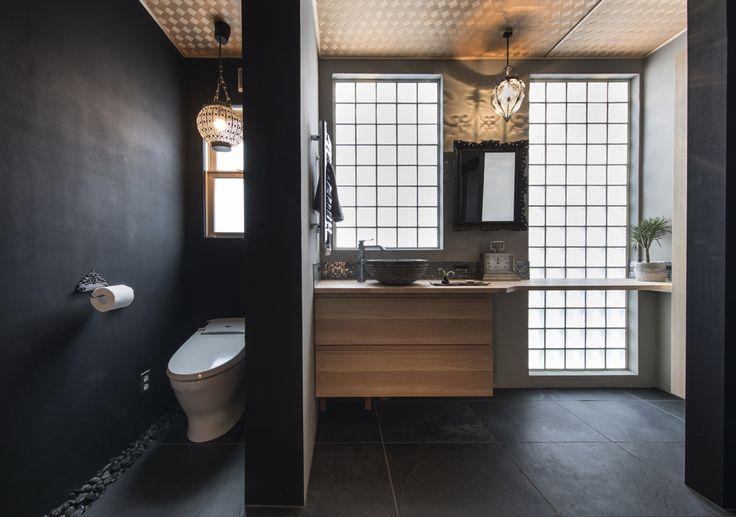 オリエンタルな香り漂うインテリアデザイン。ガラスブロックを通して自然の光が柔らかに空間を包み込みます。アジアンテイストの網代天井に、墨入モルタルと塗装で仕上げたブラックの壁のコントラストが絶妙。床は大判の大理石を貼りスッキリと。アンティークなアクセサリー小物や額縁をつけたオリジナルミラーが美しく映えます。多様な素材が調和を奏でるサニタリーのインテリアコーディネートになりました。幅広の引出し収納キャビネットに、ちょこんと乗った丸い手洗いボールがおしゃれです。バスルームへの入口は段差を無くしてバリアフリーに。ハイドアにはスモークを貼りました。