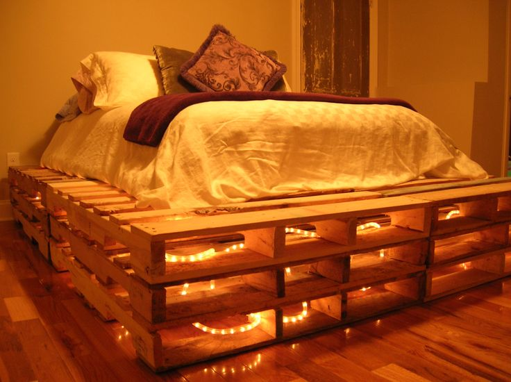 This pallet bed was so easy! We collected 12 pallets, lightly sanded and whitewashed them with watered down white paint and stacked them. I found white rope lights on clearance right after Christmas, so the entire project cost $23, including pallets! It sleeps like a dream!