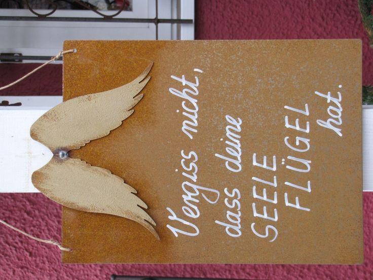 """Edelrost Schild mit goldenen Flügeln """"Vergiss nicht..."""" Wunderschönes Edelrost Schild mit goldenen Flügeln als Dekoration für Haus und Garten. Auch als Geschenk für gute Freunde und Bekannte eine tolle Idee. Das Schild ist zum Hängen und wird inkl. Bast- oder Metallband geliefert. Das Edelrost Schild ist mit folgendem Spruch versehen: """"Vergiss nicht, dass Deine Seele Flügel hat"""" Maße: Höhe: 33 cm Breite: 25 cm Preis: 20,- €"""