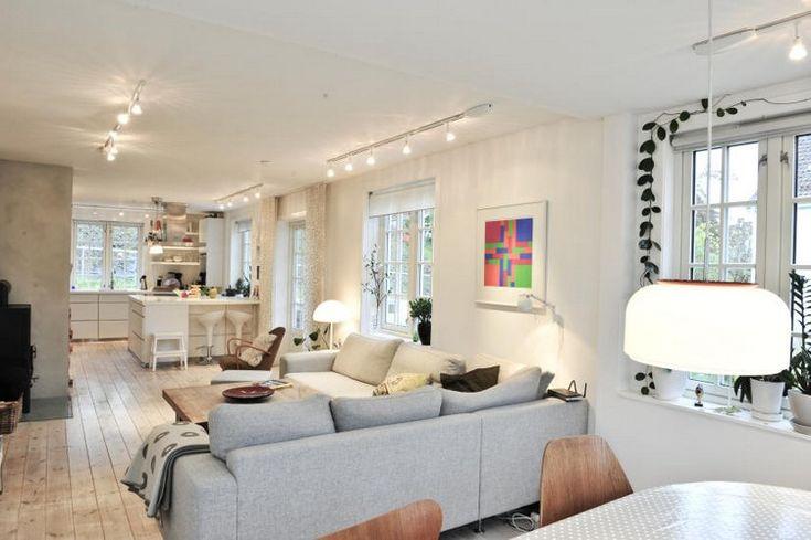 cuisine ouverte sur le salon élégant aménagé avec un canapé gris clair et une table basse en bois