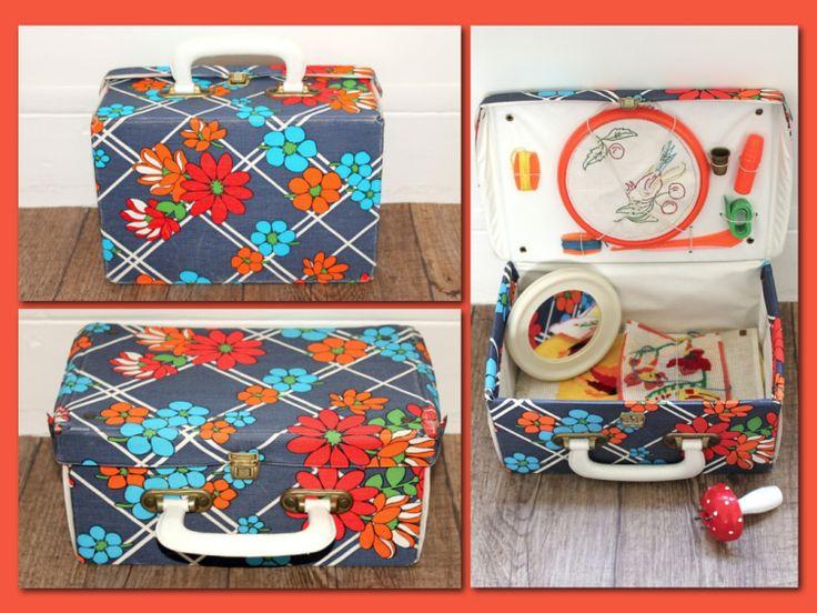 Adorable petite valise vintage contenant des canevas à moitié achevés, un cercle à broder, du fil, un mètre de couturière, un dé à coudre, un porte-aiguilles et un petit miroir.