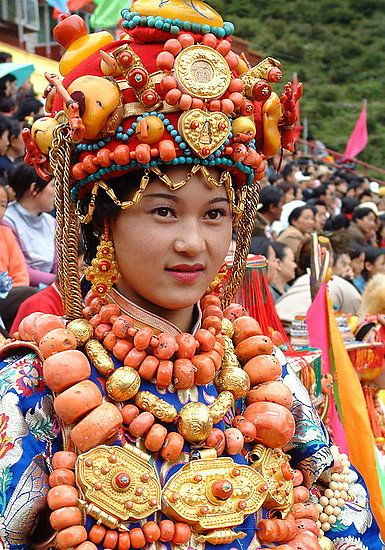 Tibet | Tibetan lady modelling an a super expensive and heavy ceremonial replete with rare gold ornaments and coral beads. Photo from the King Gesar Arts Festival / Khampa arts festival in the Kham region of Tibet in 2004. | © BetterWorld2010, via Flickr