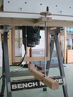 Router Lift - Homemade router lift constructed from sections of lumber, threaded rod, and T-nuts. Capable of lifting the cutter from even with the table to 1-3/8