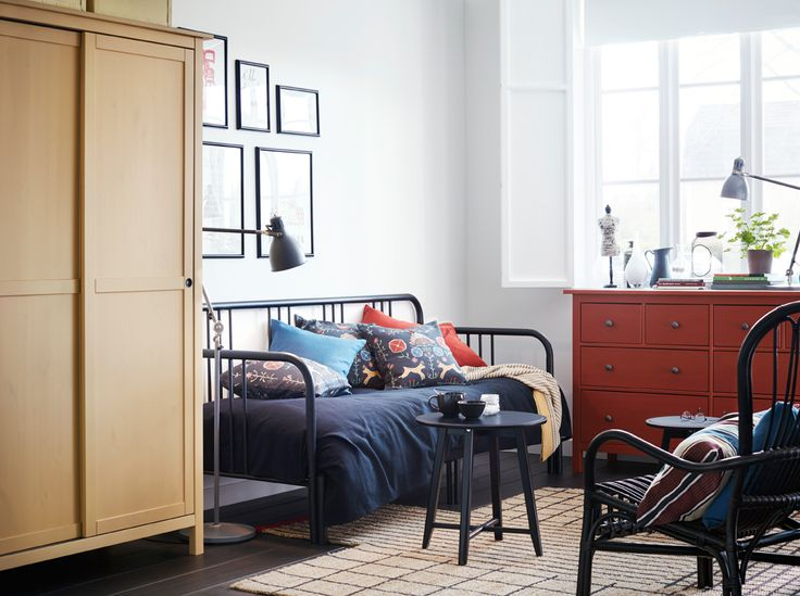 A small bedroom furnished with a day-bed for two in black metal. Shown together with a small black coffee table and a red chest of drawers with…