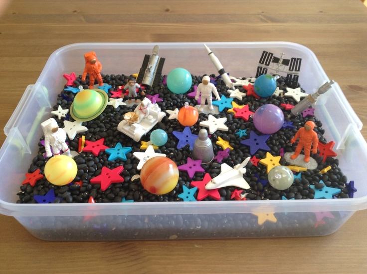 Our Space Sensory Bin.  It contains black beans, colorful star buttons from Walmart, university games 3D planets and safari space toob - Space Activity