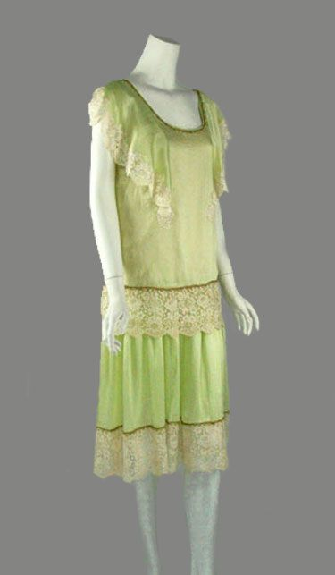 1920s mint green silk flapper dress, trimmed with off white silk/cotton lace and fine silk floss and metallic thread braid. The dress features an over tunic with scoop neckline and deeper scooped back; side floating sleeves give a cape effect. Via Palm Beach Vintage.