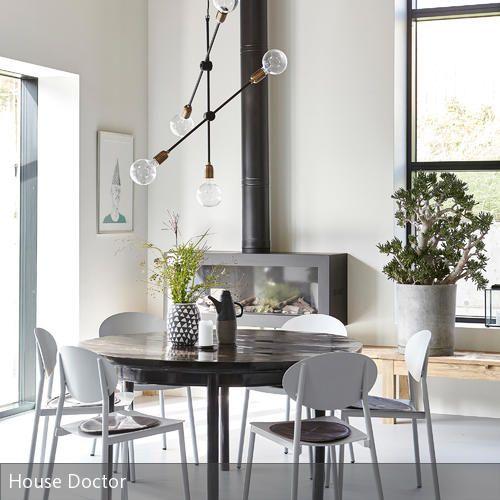 """In dem modernen Essbereich mit besonders hohen Decken bildet die Pendelleuchte """"Molecluar CB0811"""" das zentrale Element über dem runden Esstisch. Die Stühle …"""