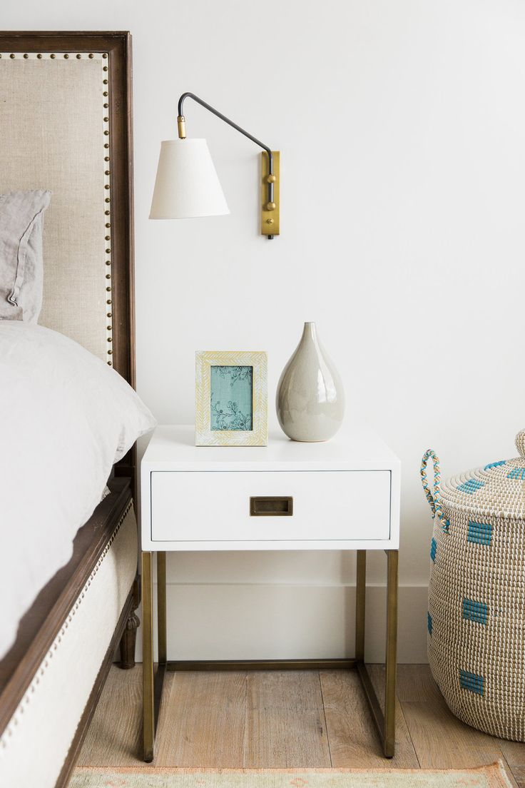 Modern white bedside storage table with metal legs and drawer // Beige and teal woven storage bin with lid / Modern wall sconce beside bed / Modern and cozy bedroom design