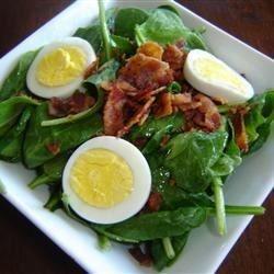 This rich and flavorful salad features fresh spinach and green onions drizzled with a warm, sweet, vinegary dressing, and sprinkled with crunchy bacon and tender bits of hard boiled egg.