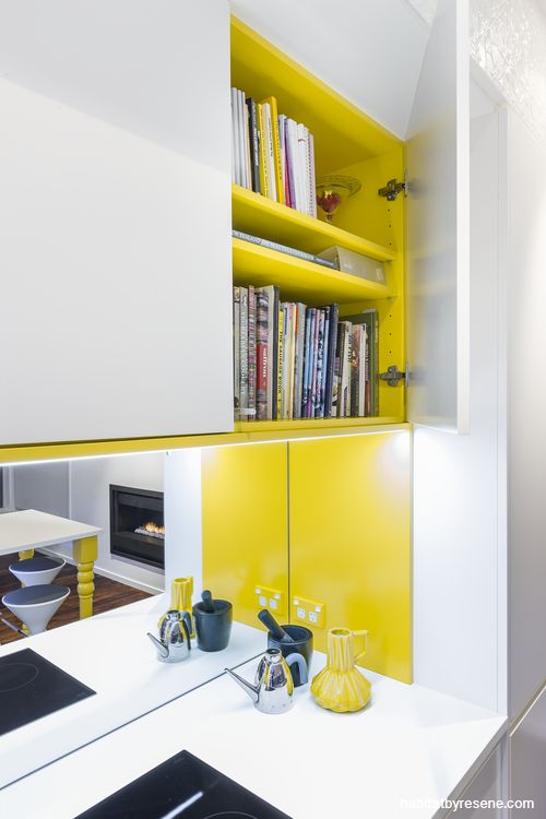 """Unexpected colour is used around the cooking area and inside the cupboard above. """"It makes you smile,"""" says designer Celia Visser. The yellow is Resene Golden Dream and the white is Resene Alabaster."""