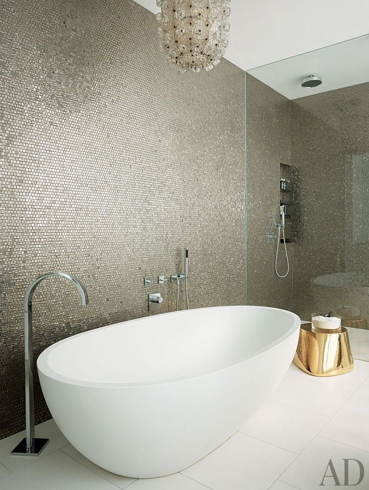 Glittering mosaic tile sheathes the walls of a master bath, which also includes a gold Moroso stool and a vintage Seguso lantern.