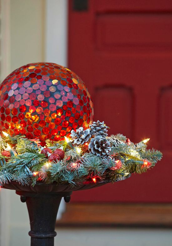 Gazing ball in bed of twinkling lights, pinecones & greenery.