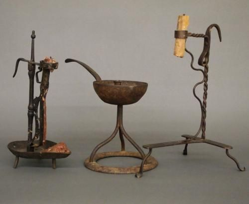 Three 19th century wrought iron items. Two candleholders with tripod bases and a grease lamp with three legs on a circular base. Some wear and oxidation. Up