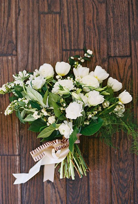 A classic bouquet comprised of white garden roses, tulips, and berries, created by The Southern Table.
