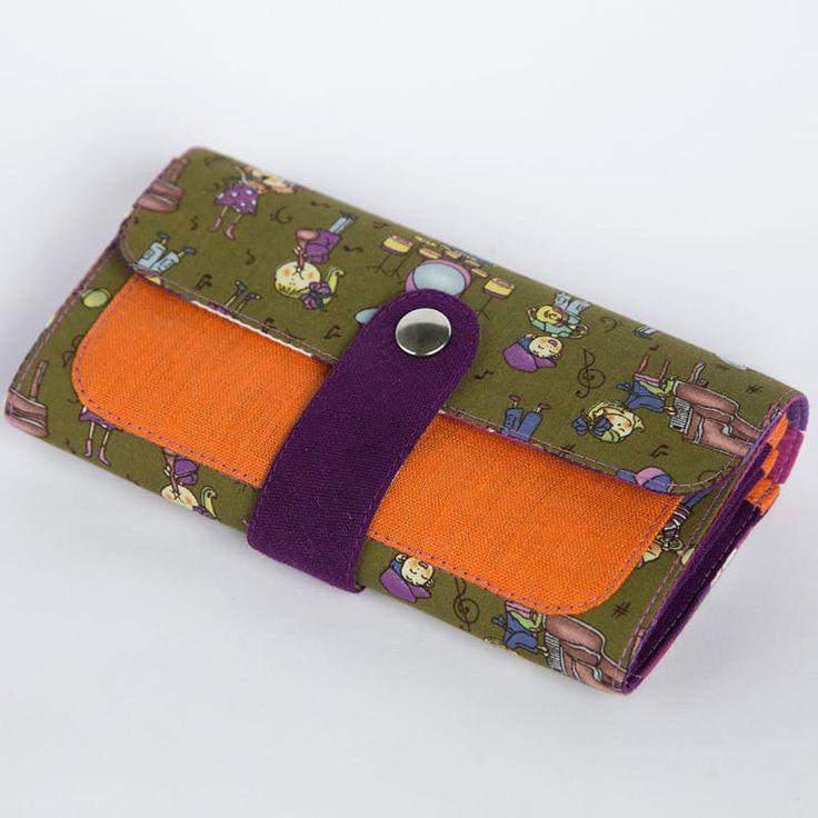 Модный женский клатч ручной работы от отечественного бренда Yak Faino, сшитый вручную мастером из трех видов натуральной ткани – джинс, лен и хлопок. Верхняя оливковая сторона клатча имеет анимационный принт малышей, играющих на музыкальных инструментах, с контрастным оранжевым наружным карман