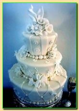 Pearlised fondant showcases twists and twirls of sugarpaste, fondant blossoms, bells, and bows.