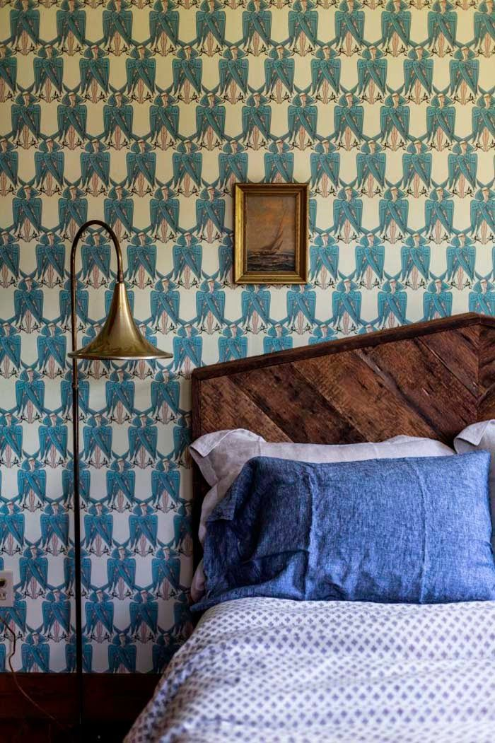 County House Bedroom With Blue Jean Colored Pillows And Patterned Wallpaper