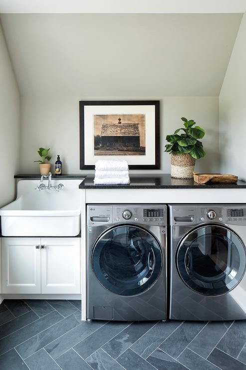 An apron laundry room sink with polished nickel faucet, mounted on white shaker cabinets is displayed to the left of an enclosed chrome washer and dryer.
