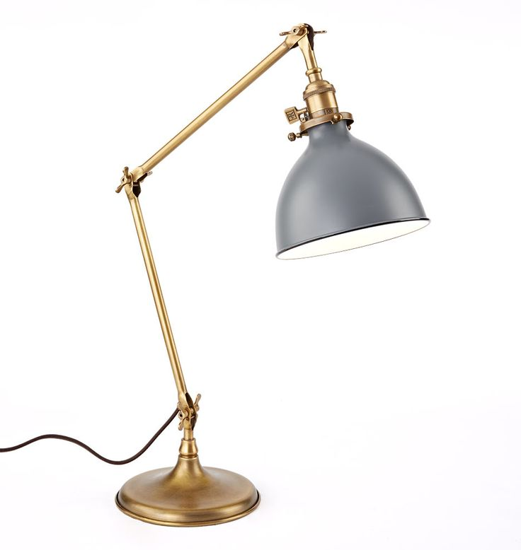 Our Grandview Task Lamp in Aged Brass updates a 1920s lamp that helped factory workers see what they were doing. It features a triple-jointed arm, a weighted base that resists tipping, and a felt bottom that won't scratch surfaces.  * Spun brass parts, painted metal shade, cloth cord * Brass turnkey switch at socket * Imported