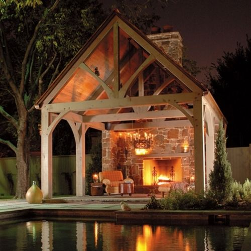 Outdoor fireplace covered with a timber frame porch
