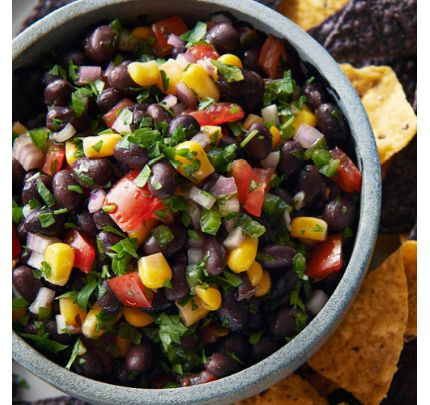 Beaucoup de croustilles autour d'un bol de salsa aux tomates, haricots noirs et maïs avec jalapenos