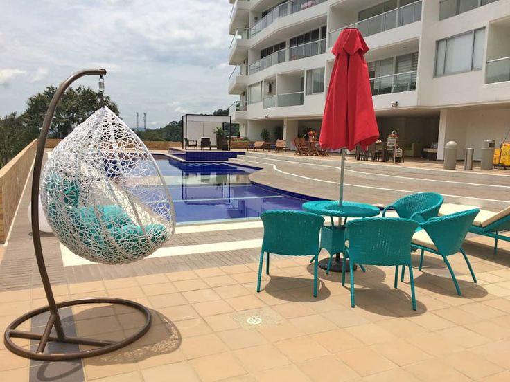 Knallig türkise Rattanmöbel für den Pool von FARIAS SAS ARQUITECTOS