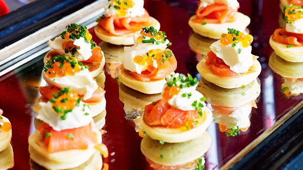 Blini with smoked salmon. The mixture in this recipe is a little thick, I added a bit more milk to make the batter a dropping consistency so that the teaspoonful dropped in the pan formed a round just the right size for serving as a canape. Makes about 50.