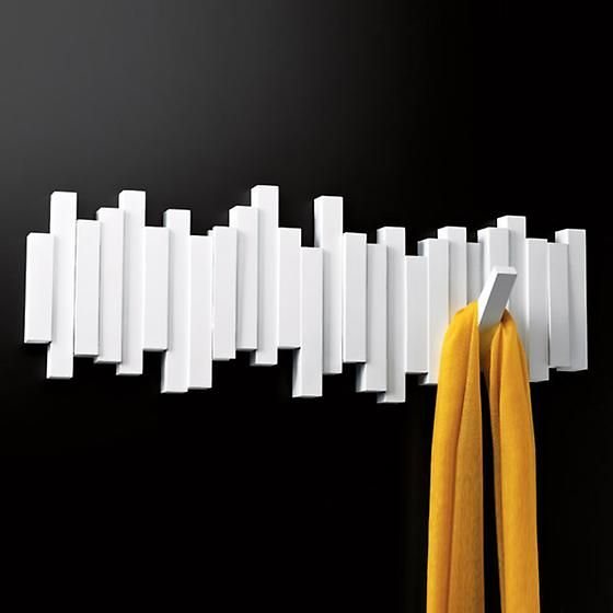 """The beauty of the polished Sticks Multi-Hook Rack by Umbra is what you don't see. When not in use, the five hooks fold flat so all that's visible is a sleek, sculptural design. You can flip each hook down as needed to hang coats, jackets, scarves and hats. It's perfect for narrow spaces. <a href=""""/category/umbra"""">Shop all Umbra</a>."""