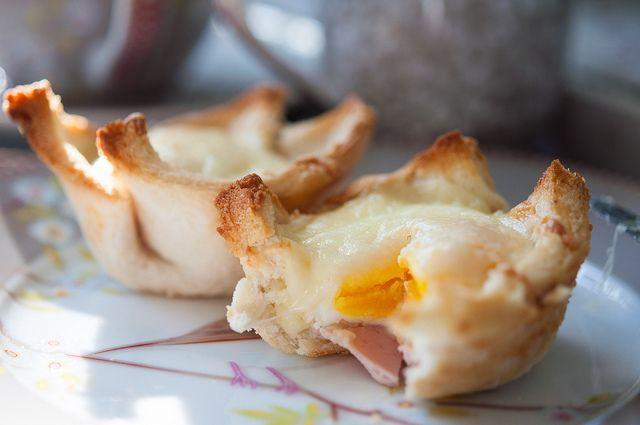 Toastbrot entrinden, einmal flach auswalzen, mit flüssiger Butter an allen Seiten, vorallem an den Ecke bestreichen. In ein Muffinförmchen legen, ein kleines Scheibchen Schinken hineinlegen, ein kleines Ei einfüllen, mit Bechamel auffüllen und mit geriebenem Käse bestreuen. Im Backrohr solange backen, bis die Ecken schon braun und das Ei nach Wunsch ist. fertig - lecker.