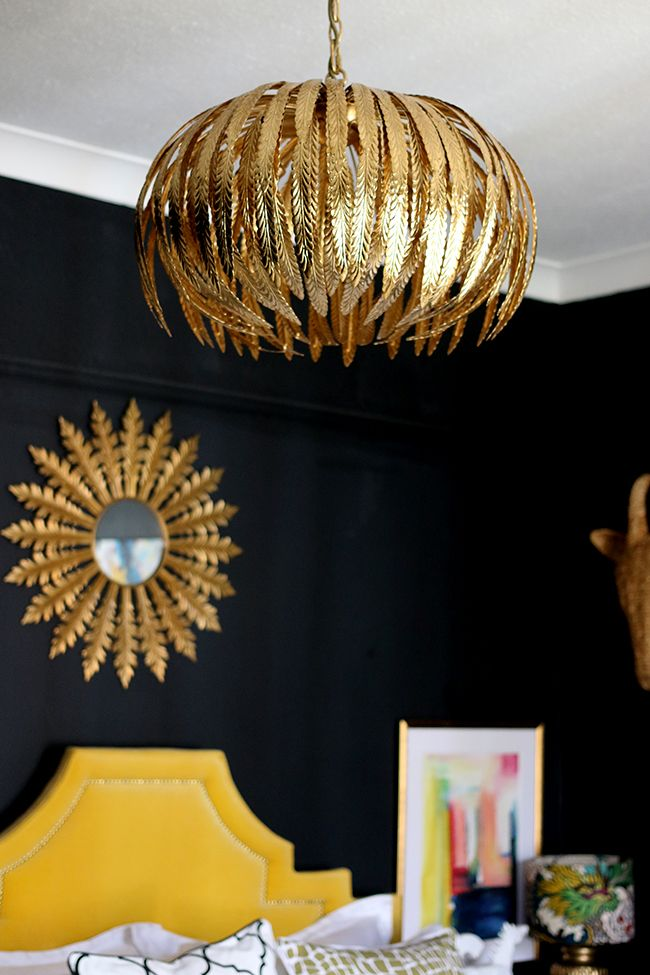 black bedroom with gold light fixture, yellow headboard and colourful artwork - see more on www.swoonworthy.co.uk