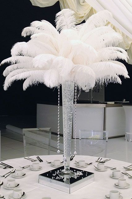 Tall Lily Vase filled with clear or coloured gel with 25 pure ostrich feathers and 4 crystal drops lit using a wireless LED light system in the base.