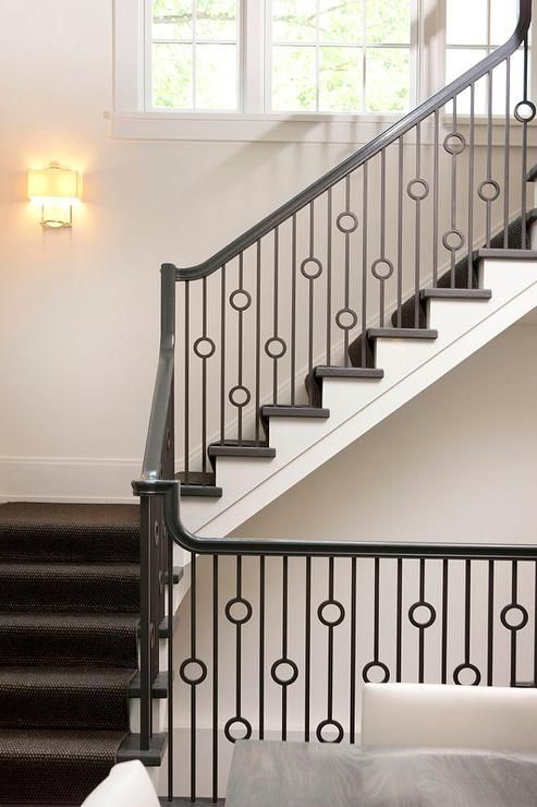 Lovely staircase features a dark jute stair runner and an iron hand rail and iron circles spindles.
