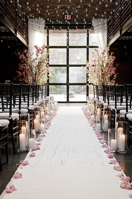 Tall candle holders with pink flowers line the aisle at this indoor fall wedding.