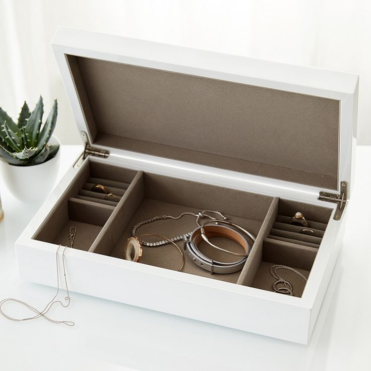 Beautifully simple and wonderfully practical, this sleek, white lacquer lidded jewellery box is designed to perfectly hold all of your necklaces, rings, earrings and bracelets within organised internal compartments. What makes this jewellery box so special is that it can be stacked upon our matching White Lacquer Jewellery Trays (sold separately), so you can make your box bigger as your jewellery collection grows. Finished with a slatted base, this box will sit seamlessly upon as many trays…