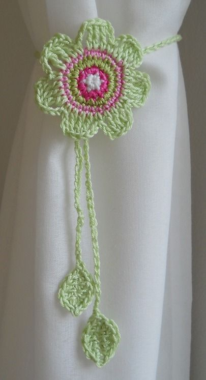 .A pretty green and pink handmade crochet flower for a curtain tie-back - cute Bohemian or country decorating touch!