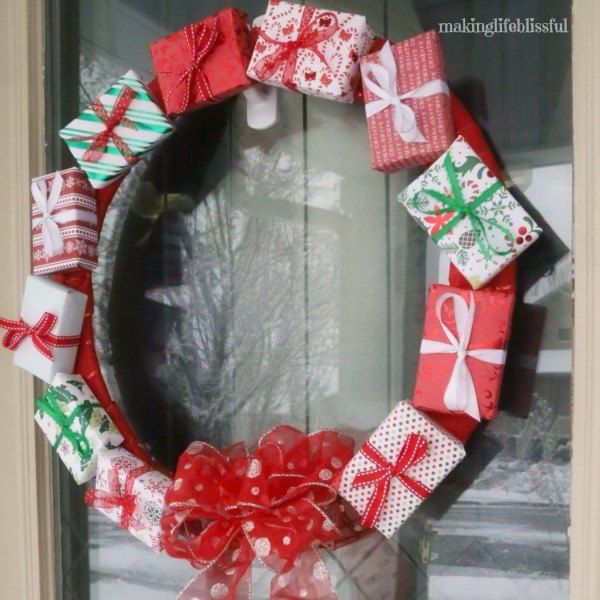 DIY Gift Box Christmas Wreath Tutorial - I love scrapbook paper. Even though my scrapbooking days are over, I can't help but visit the paper aisle at my craft store and wish I had some project to do with it. So I came up with a Gift Box Wreath that is fairly simple and uses your scrapbook paper (even just the leftovers, if you want). You can also use wrapping paper.