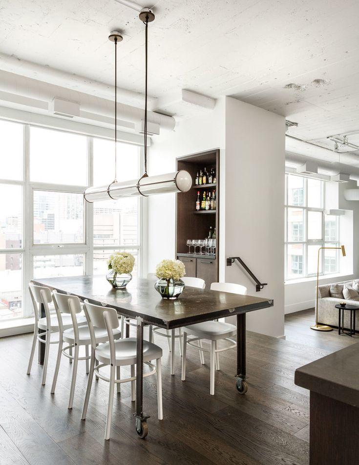 В центре столовой расположен уникальный выполненный на заказ стальной обеденный стол с бетонной столешницей.  (архитектура,дизайн,экстерьер,интерьер,дизайн интерьера,мебель,индустриальный,лофт,винтаж,стиль лофт,индустриальный стиль,квартиры,апартаменты) .