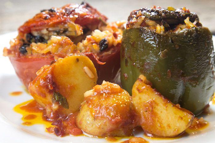 Ντομάτες και πιπεριές γεμιστές,12 μικρομεσαίες πιπεριές πράσινες σκούρες 12 μικρομεσαίες ντομάτες 2 ½ φλ. ρύζι μακρύκοκκο Parboiled (συστήνω Agrino). Κάθε ζευγάρι γεμιστών (ντομάτα-πιπεριά) χρειάζεται 2/10 του φλυτζανιού ρύζι. Στα 5 ζευγάρια, άρα χρειάζεται 1 φλυτζάνι 2 μεσαία κρεμμύδια ψιλοκομμένα 4-5 πατάτες κομμένες σε κομμάτια 3 cm 800 γρ. χυμό ντομάτας (2 κουτιά) 140 γρ. ντοματοπολτό (2 συσκευασίες των 70 γρ.) 60 γρ. μαύρη σταφίδα 50 γρ. κουκουνάρι 4 κ.σ. ψιλοκομμένο μαϊντανό (μισ