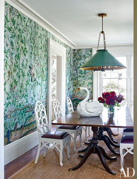A leafy antique wallpaper lines the dining room, where a swan tureen from John Rosselli Antiques tops a table ringed by Frances Elkins–style chairs from Kevin L. Perry; the star sconce is by Frederick P. Victoria & Son.