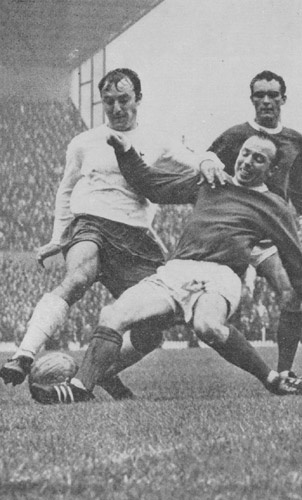 James 'Jimmy' Greaves (Tottenham Hotspur FC, 1961–1970, 321 apps, 220 goals) received a tackle by Nobby Stiles (Manchester United, 1960–1971, 311 apps, 17 goals).