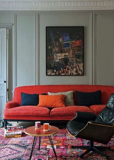 oversized orange sofa, kilim, midcentury chair, traditional wall panelling and crown molding = eclectic