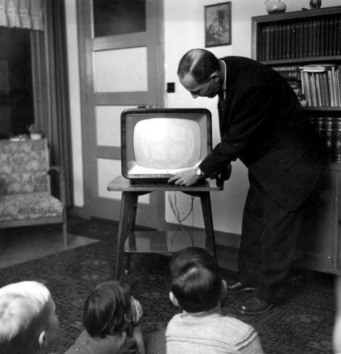 Man zet de televisie aan, drie kinderen wachten vol spanning. Nederland, ca, 1960. Televisie kijken.