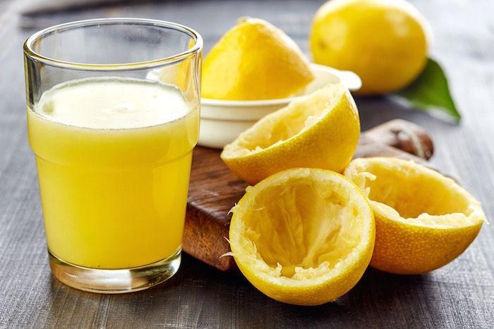 Frissen kifacsart citromlé üvegpohárban, mellette a facsaró és citromok.