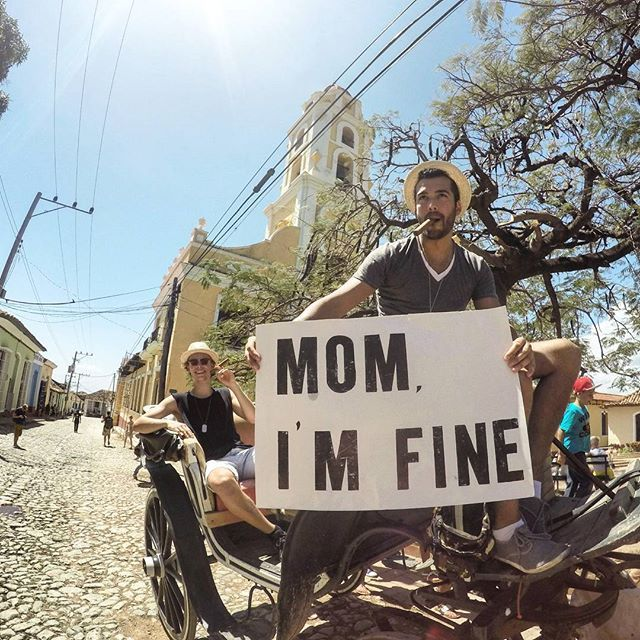 """Pin for Later: 1 Guy Travels the World With a """"Mom I'm Fine"""" Sign While Casually Looking Fine AF"""