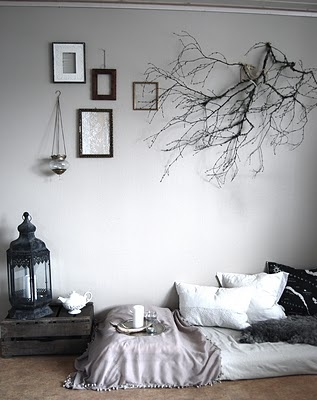 Eldrid created a feeling of sitting underneath a tree by bringing nature indoors & hanging a tree branch above a sitting area.