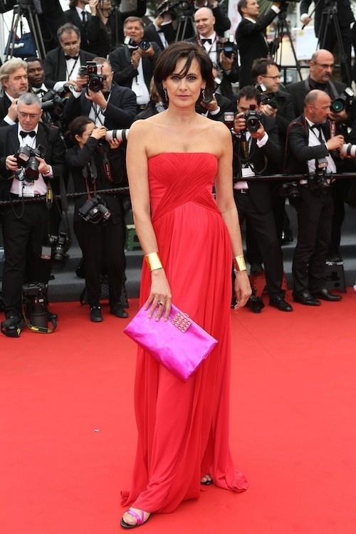 Cannes 2013 - Inés de la Fressange con su modelo en color rojo pasión en escote palabra de honor y cruzado y un maxi clutch en rosa fucsia a conjunto de sus sandalias.