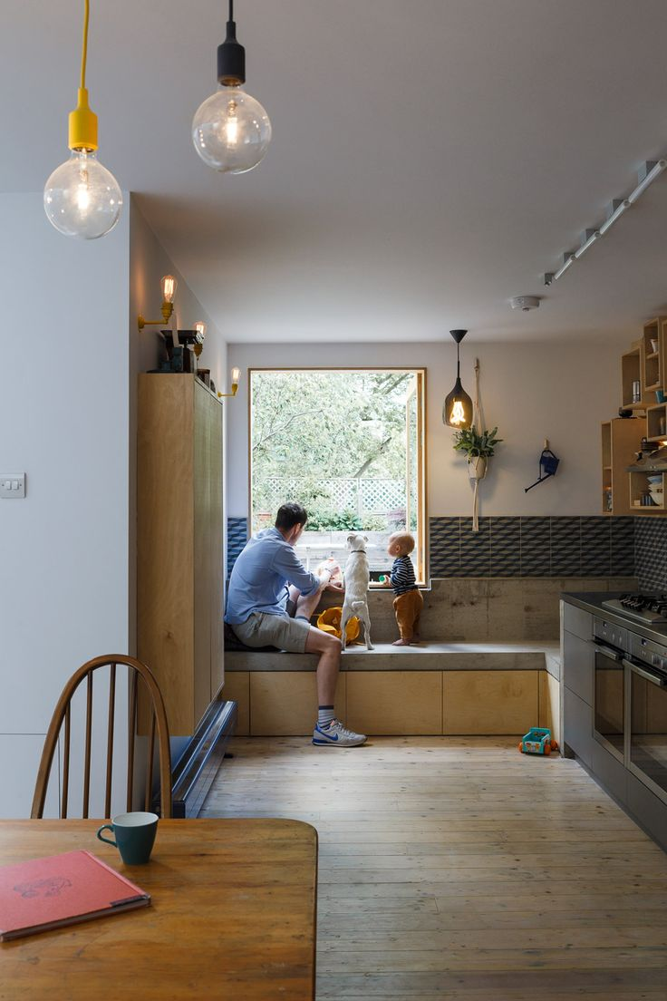 A concrete window seat, geometric tiles and a storage wall made of wooden boxes feature inside this east London house