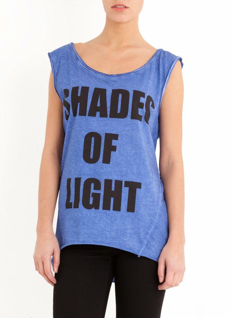 Wijdvallende, mouwloze top met zwarte print 'Shades Of Light'. Bij de schouders, hals, en onderkant van de top zijn de onafgewerkte zoomen zichtbaar. Combineer dit item met een donkere skinny jeans of shortje.