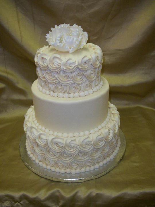 Elegant rosette wedding cake all in buttercream. Fondant peony on top.