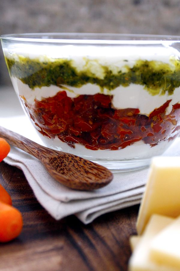 An Italian dip with a stunning presentation and a flavorful bite. Fragrant basil pesto, intensely sweet sun-dried tomatoes and a combination of creamy goat cheese and mild cream cheese. Serve with tortilla chips, Bruschetta Crisps or veggies!